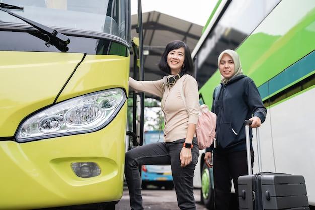 Close-up van een kortharige vrouw met koptelefoon en een tas die lacht terwijl ze naar de busdeur loopt met een vrouw in een sluier die een koffer achter zich draagt als ze in de bus gaat