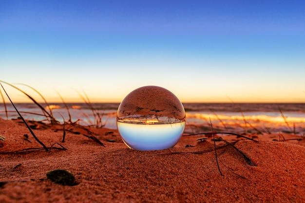 Close-up van een kristallen bol op het strand met de omgeving die erover nadenkt