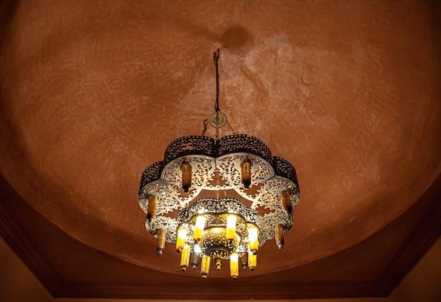 Close-up van een kroonluchter aan het plafond met een traditionele oosterse stijl met veel details
