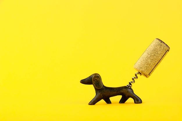 Close-up van een kurkentrekker in de vorm van een teckelhond met een wijnkurk in de vorm van een staart op een gele achtergrond. ruimte kopiëren.