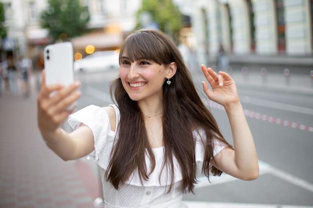 Close-up van een lachend brunette meisje dat via een videogesprek via een telefoon communiceert en haar hand zwaait naar de camera op de achtergrond van de straat