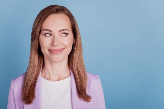 Close-up van een lachende vrouw, kijk naar de lege ruimte op de blauwe muur