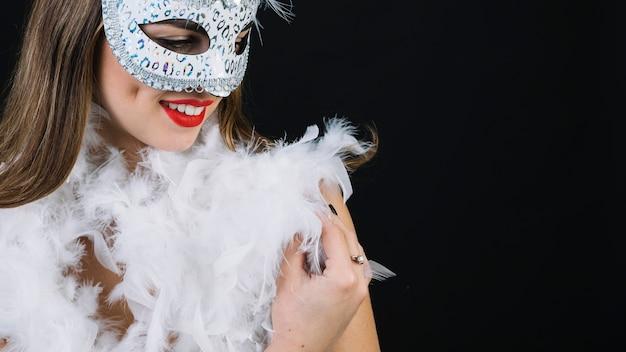 Close-up van een lachende vrouw met carnaval masker en boa veer op zwarte achtergrond