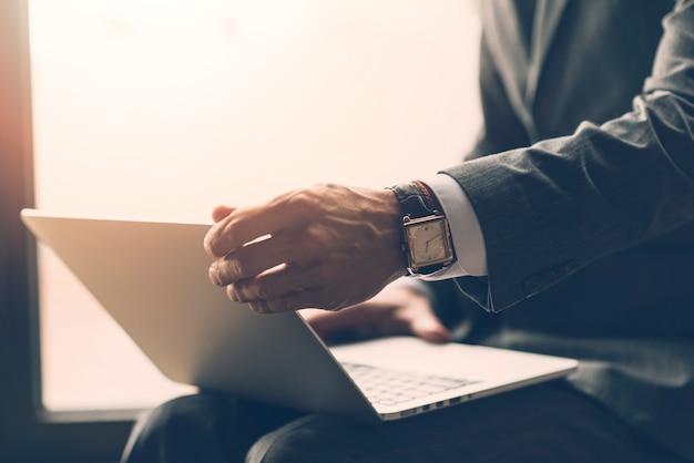 Close-up van een laptop van de zakenmanholding op zijn overlapping