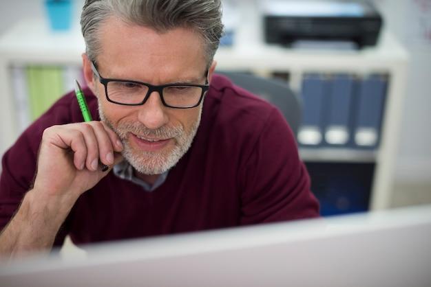 Close up van een man aan het werk op de computer