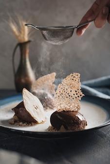 Close-up van een man afstoffen de suiker op heerlijke chocolade gebak