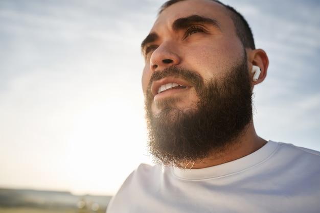 Close up van een man atleet die naar muziek luistert tijdens een wandeling op het platteland