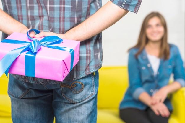 Close-up van een man de doos van de gift van de hand te verbergen achter zijn rug