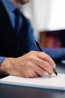 Close-up van een man die aantekeningen maakt op een notebook terwijl hij thuis werkt