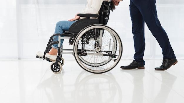 Close-up van een man die de vrouwenzitting op rolstoel duwt