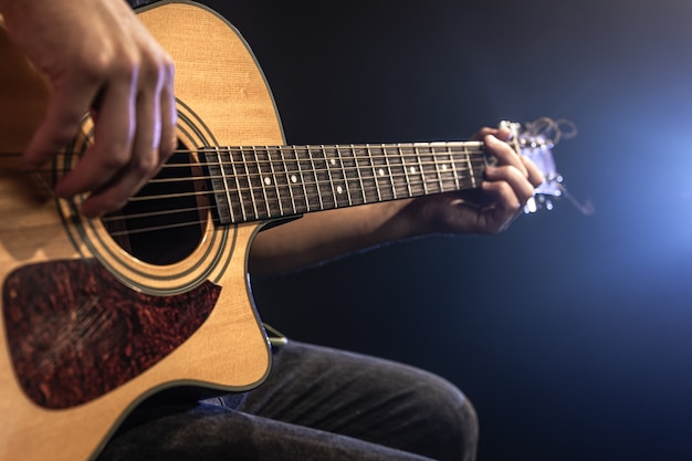 Close-up van een man die een akoestische gitaar speelt in het donker met toneelverlichting.