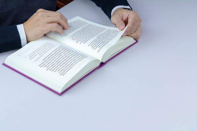 Close-up van een man die een boek in de bibliotheek leest.