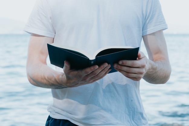 Close-up van een man die een boek vasthoudt tijdens het lezen, religieuze en studieconcepten, strand en heldere dag