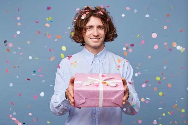 Close up van een man die een cadeau geeft in een roze doos met wit lint