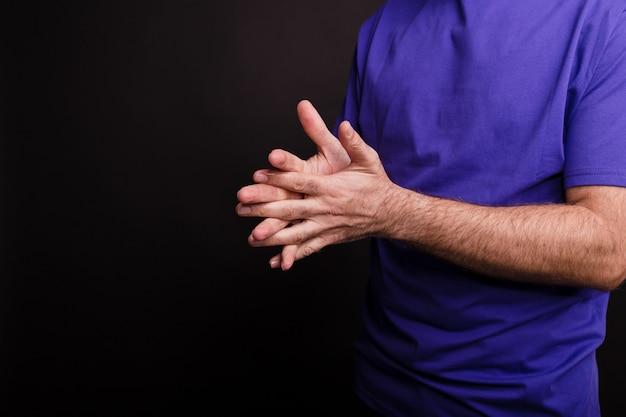 Close-up van een man die een handdesinfectiemiddel gebruikt tegen een zwarte achtergrond - covid-19