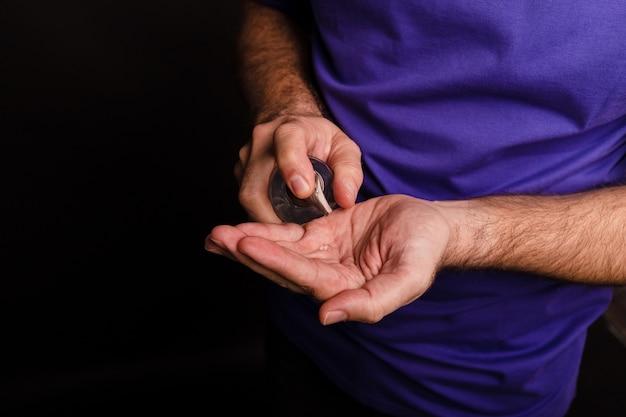 Close-up van een man die een handdesinfectiemiddel op zwart gebruikt