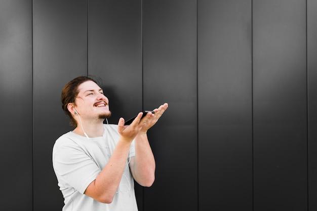 Close-up van een man die geniet van de muziek op mobiele telefoon via oortelefoons