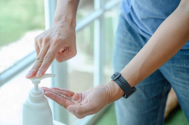 Close-up van een man die handdesinfecterend middel 1 fles alcoholdesinfecterend middel gebruikt voor bescherming tegen het nieuwe coronavirus covid19, handdesinfecterend middel en gezondheidsconcept.