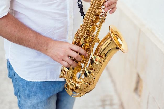 Close up van een man die hartstochtelijk zijn saxofoon op straat speelt