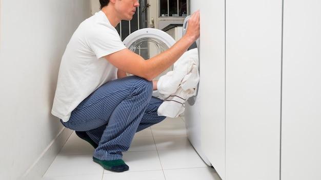 Close-up van een man die kleren in de wasmachine zet