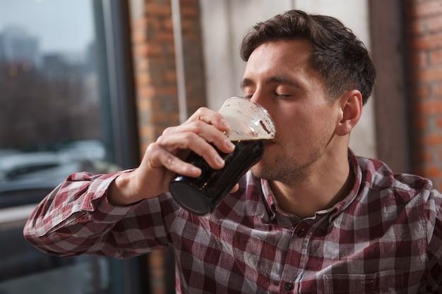 Close-up van een man die lekker ambachtelijk bier nipt met zijn ogen dicht van plezier
