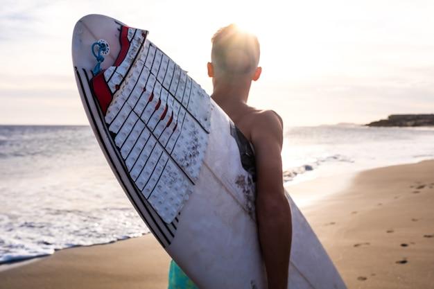Close-up van een man die op het strand loopt met zijn surfplank die in de zomer gaat surfen met de zonsondergang