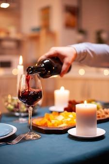 Close-up van een man die wijn in glas giet tijdens een romantisch diner met zijn vrouw in de eetkamer. jonge man die rode wijn in het glas van de vrouw giet. romantisch kaukasisch gelukkig paar zittend aan tafel vieren.