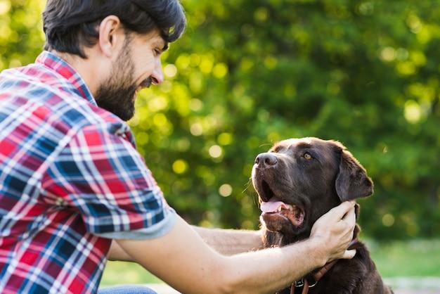 Close-up van een man die zijn hond aait