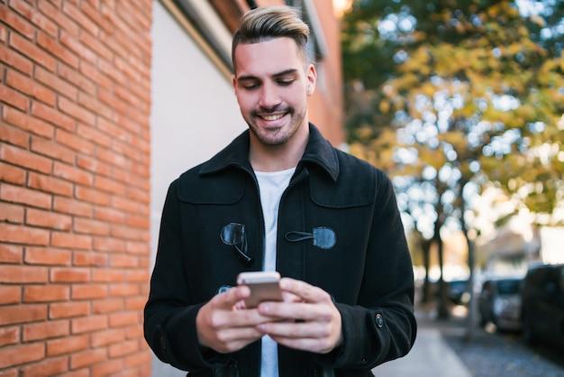 Close-up van een man die zijn mobiele telefoon gebruikt terwijl hij buiten op straat loopt