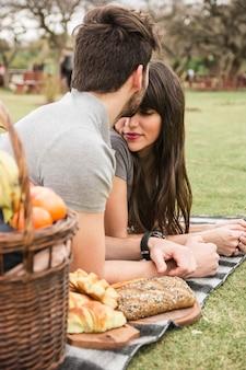 Close-up van een man die zijn vriendin op het voorhoofd kussen in het park