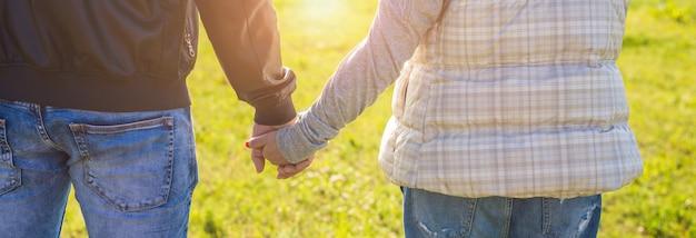 Close up van een man en een vrouw hand in hand buiten