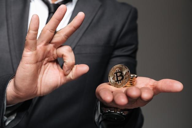 Close up van een man gekleed in pak met bitcoin