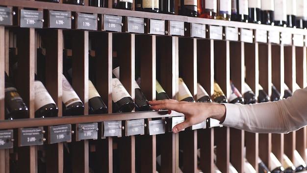Close-up van een man hand die een fles wijn van een plank in een opslag selecteert