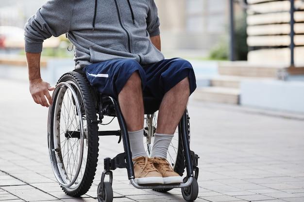 Close-up van een man in casual kleding die buiten in een rolstoel zit