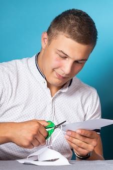 Close-up van een man in een wit overhemd die huiswerk uit papier snijdt