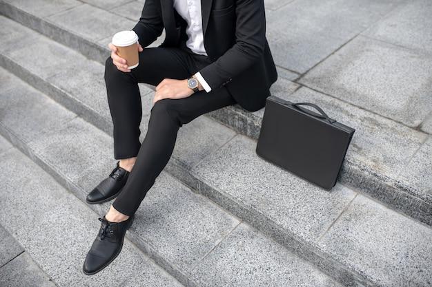 Close up van een man in zwart pak met een koffiekopje in de hand