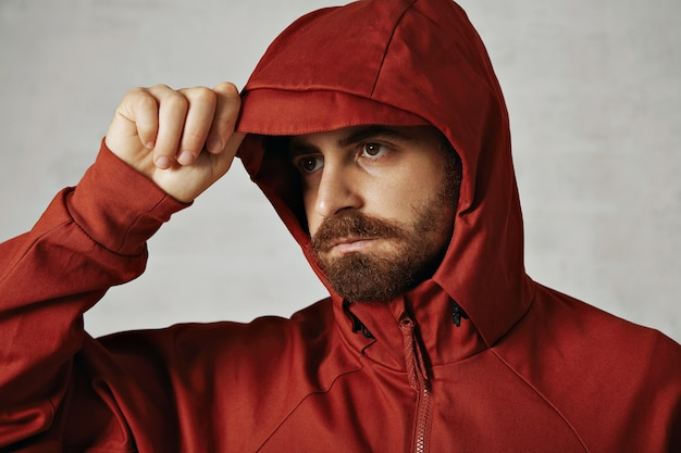 Close up van een man met baard aanpassen van de kap van zijn rode anorak op wit wordt geïsoleerd