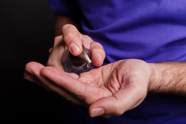 Close-up van een man met behulp van een handdesinfecterend middel op zwart