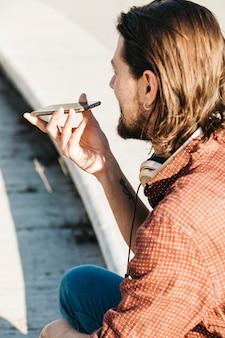 Close-up van een man met behulp van slimme telefoon spraakherkenning on-line