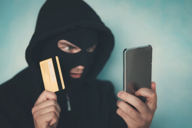 Close-up van een man met een overvalmasker en capuchon die de creditcard vasthoudt en naar het smartphonescherm kijkt. mannelijke crimineel regelt een financiële affaire met mobiel en creditcard. gevaren van netwerkfraude.