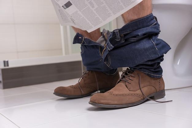 Close-up van een man met jeans en schoenen die de krant leest terwijl hij op de wc-bril zit in de moderne betegelde badkamer thuis