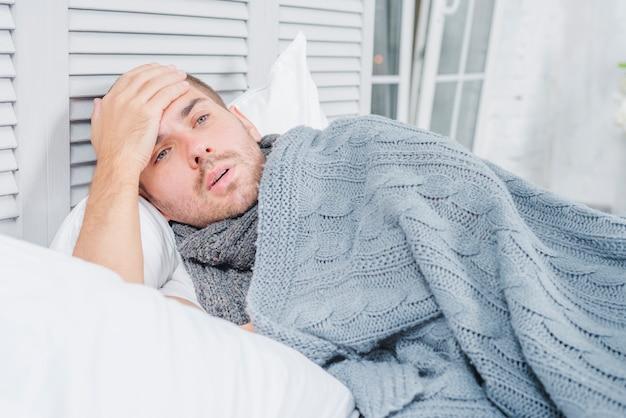 Close-up van een man met koorts zijn voorhoofd met de hand aan te raken