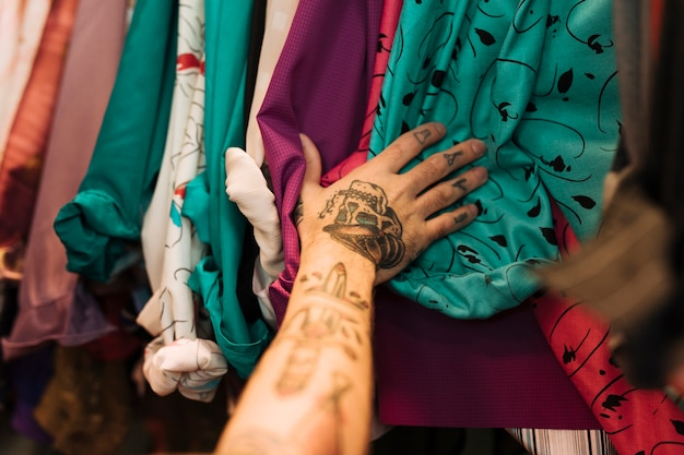 Close-up van een man met tatoeage op zijn hand aanraken van shirts op het spoor gerangschikt