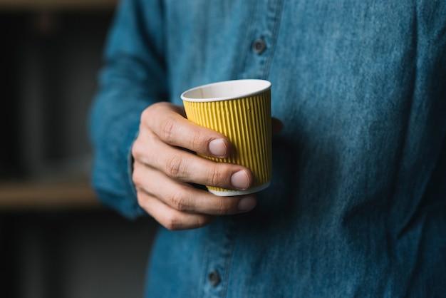 Close-up van een man's hand met wegwerp koffiekopje