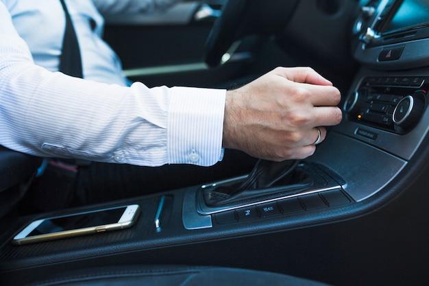 Close-up van een man's hand veranderende versnelling in de auto
