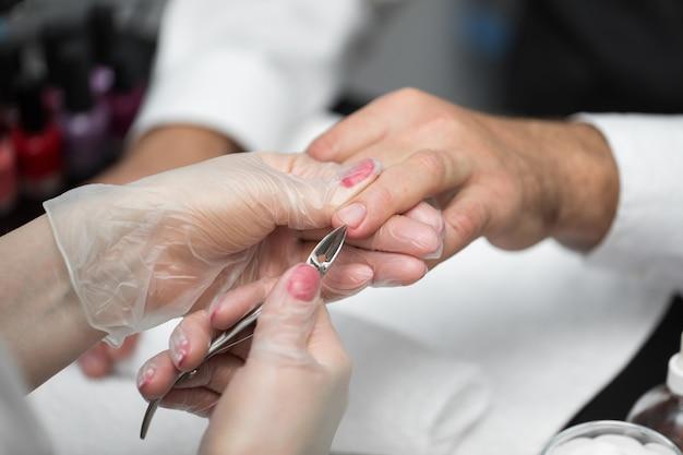Close-up van een manicure die de cuticula van de vingers van de persoon afsnijdt