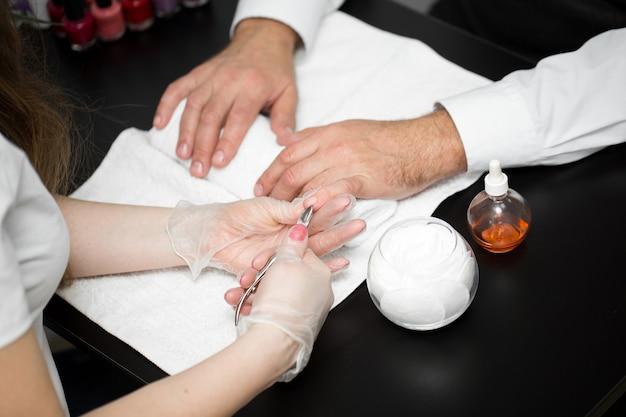 Close-up van een manicure die de nagelriem van de vingers van de persoon afsnijdt
