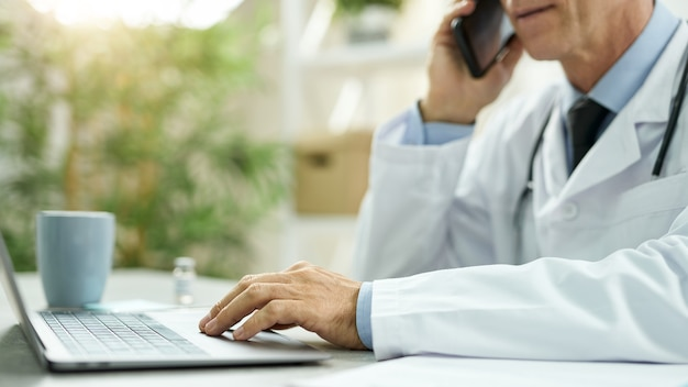 Close-up van een mannelijke arts die aan tafel zit en aan een notebook werkt terwijl hij een telefoongesprek voert in de kliniek