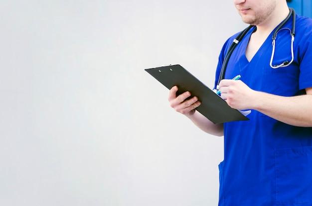 Close-up van een mannelijke arts die het klembord met pen onderzoekt die tegen grijze achtergrond wordt geïsoleerd