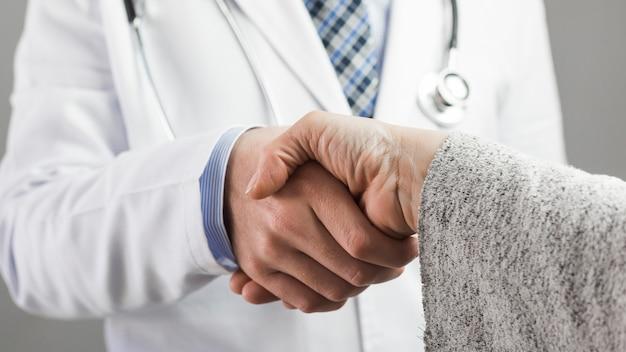 Close-up van een mannelijke arts en een patiënt handen schudden